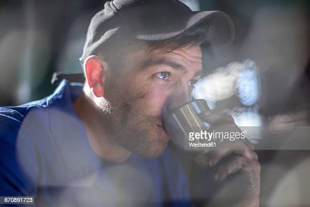 mechanic in workshop having coffee break - kunsthandwerker stock-fotos und bilder