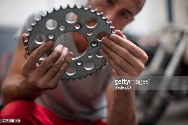 Mechanic in workshop holding a sprocket