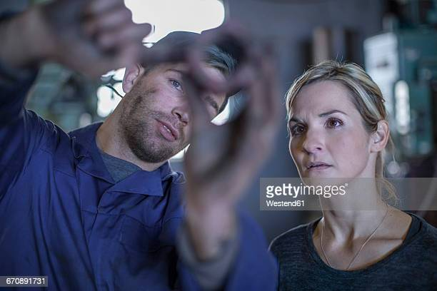 Mechanic in workshop showing object to woman