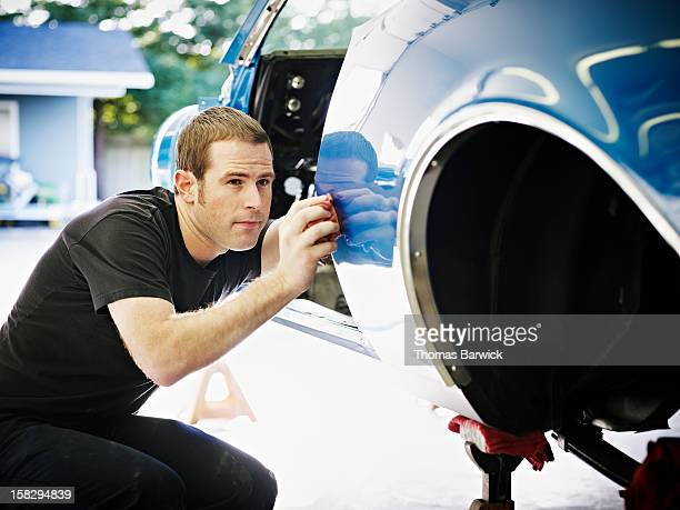 Mechanic inspecting side of car being restored