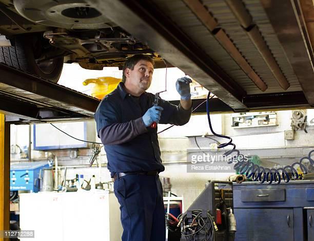 Mechanic investigates under car.