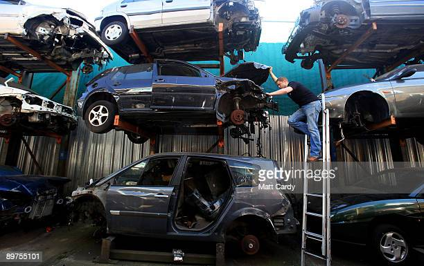 A mechanic looks for parts from cars that are stacked awaiting dismantling and recycling at CMS Vehicle Solutions Ltd on August 11 2009 in Gloucester...