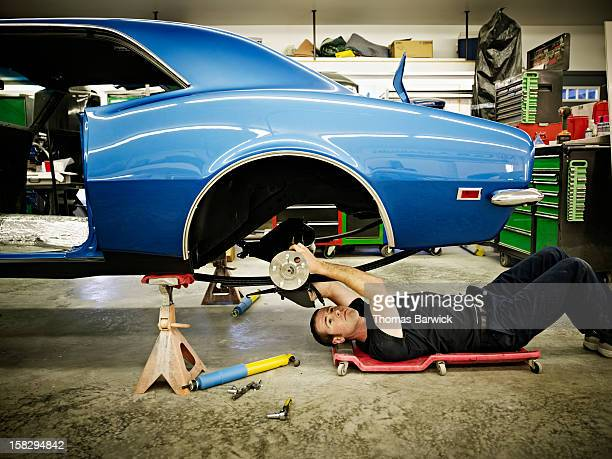 Mechanic lying on floor in garage working on car