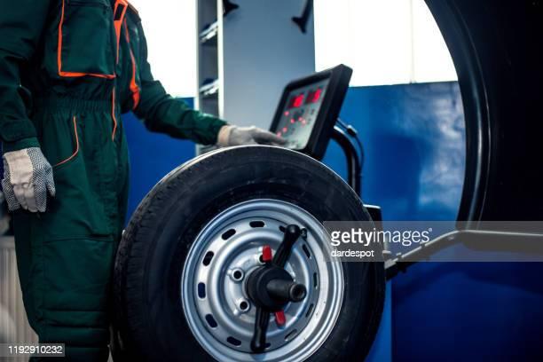 mechanic man working on balancing machine - wheel stock pictures, royalty-free photos & images