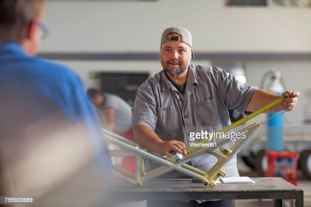 Mechanic measuring car unit in workshop