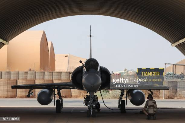 A mechanic of the French Air Force works on a Mirage 2000 aircraft before it took off from the French Air Force base in Niamey on December 22 to...