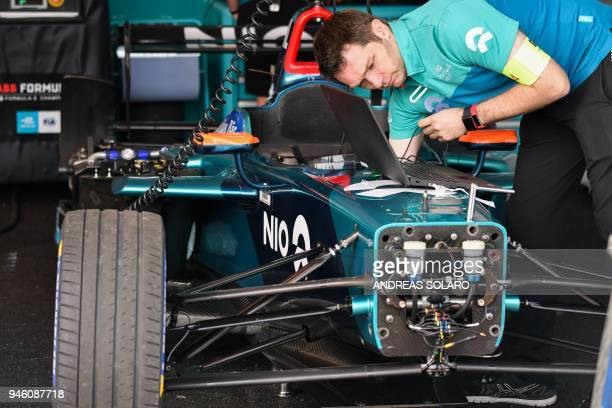 A mechanic of the NextEV team works on an electric race car in the pit before the start of the Rome leg of the Formula E electric car championship in...