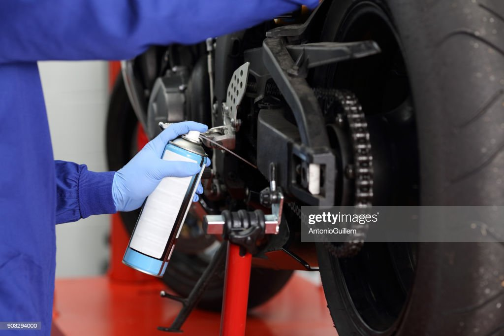 Mechanic oiling a motorcycle chain : Stock Photo