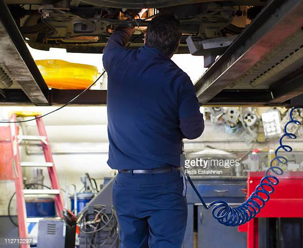 Mechanic peers under auto with light