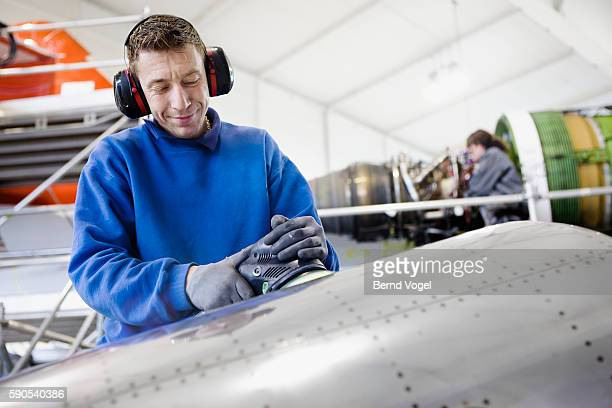 mechanic polishing airplane at factory - aircraft assembly plant stock pictures, royalty-free photos & images