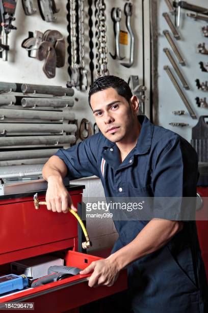 Mechanic posing by a tool box looking at the camera