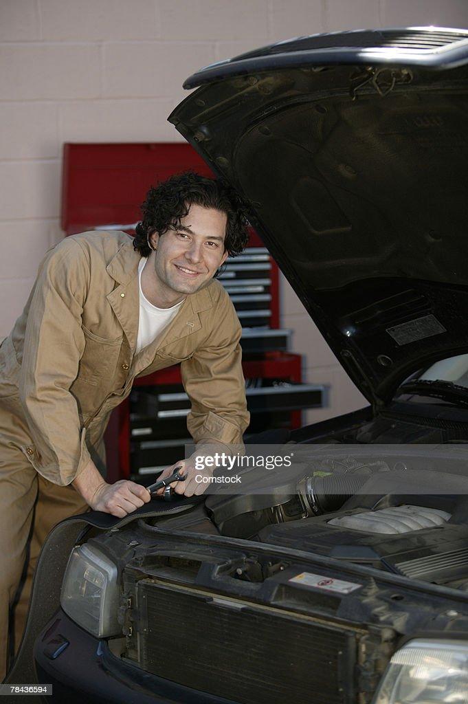 Mechanic posing with car in shop : Foto de stock