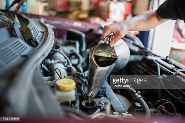 Mechanic pouring liquid into car