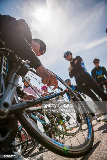 Mechanic prepares a tire as teenager members of the Z3 Triathlon team stand watching in West Des Moines, IA.