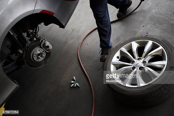 A mechanic prepares to perform a tire rotation on a customer vehicle at a Pep Boys Manny Moe Jack service center in Clarksville Indiana US on...