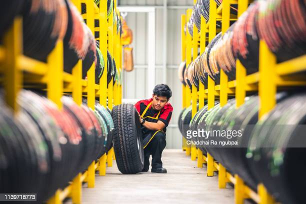mechanic pulls tire from the tyre store warehouse - vehicle part stock pictures, royalty-free photos & images