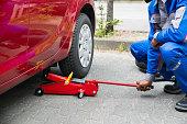 Mechanic Putting Hydraulic Floor Jack Inside The Car