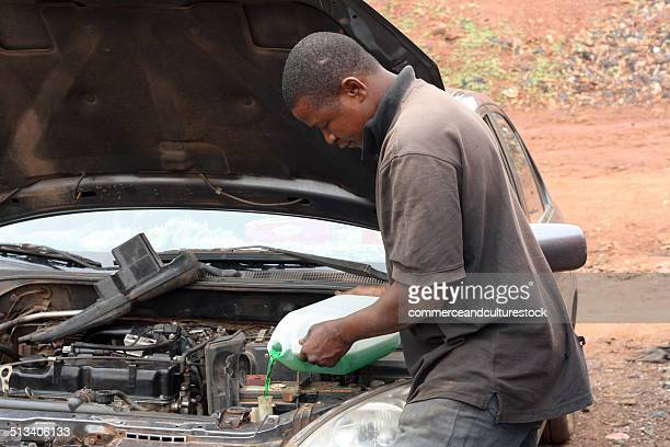 a mechanic putting water in radiator - vehicle grille stock pictures, royalty-free photos & images