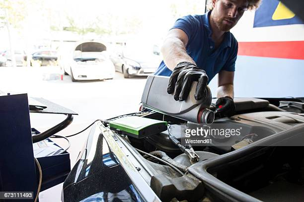 mechanic refilling oil in a car - oil change stock pictures, royalty-free photos & images