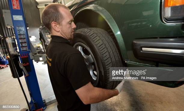 Mechanic removes a wheel from a Bentley car in his workshop