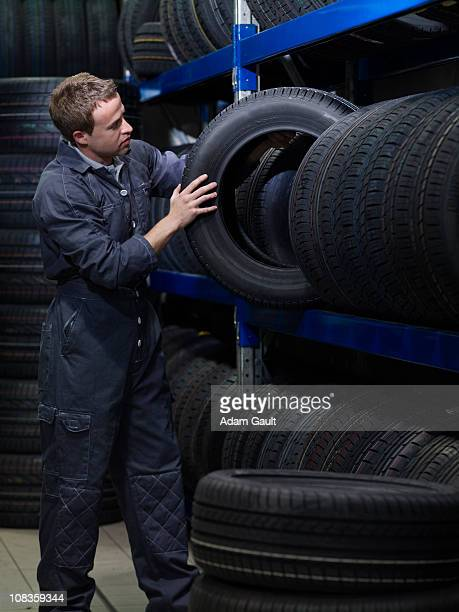 Mechanic removing tire from rack
