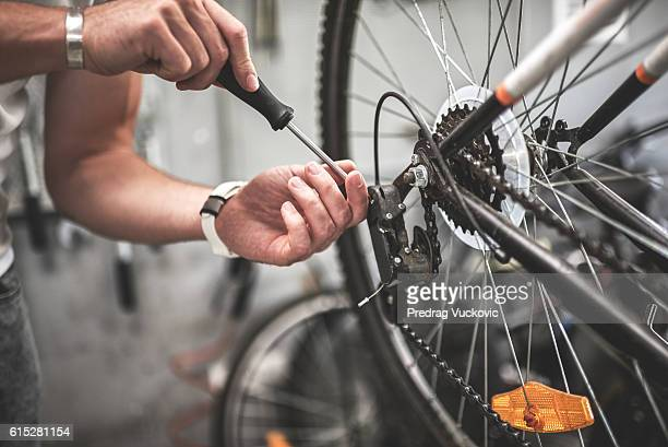 mechanic repairing bicycle rear wheel - fietsen stockfoto's en -beelden