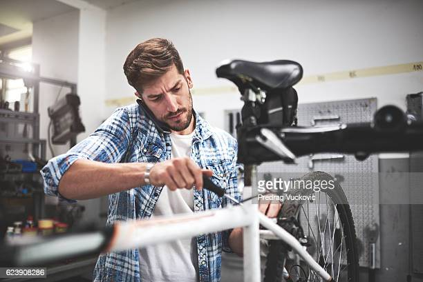 Mechanic repairing bicycle wheel