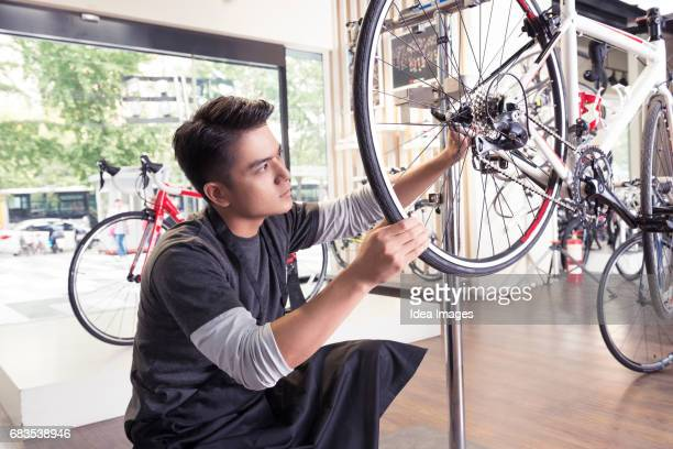 Mechanic repairing bike in workshop