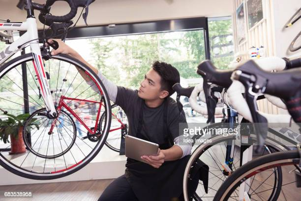 mechanic repairing bike in workshop - bicycle shop stock pictures, royalty-free photos & images