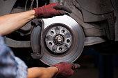Mechanic repairing brakes on a car