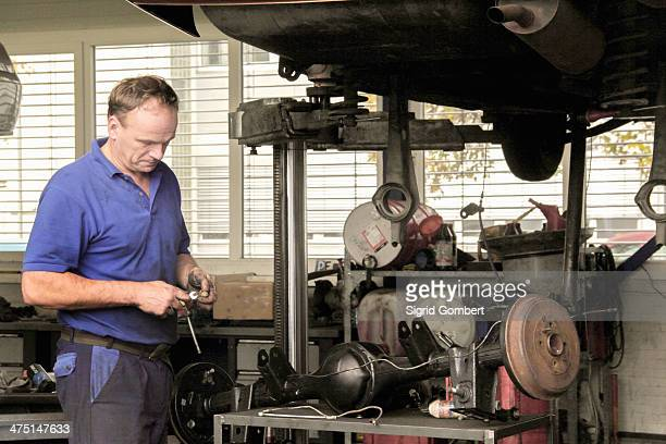 mechanic repairing car in workshop - sigrid gombert stock pictures, royalty-free photos & images