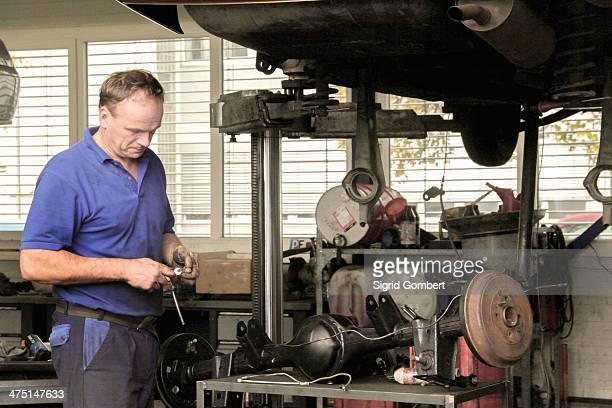 mechanic repairing car in workshop - sigrid gombert stockfoto's en -beelden