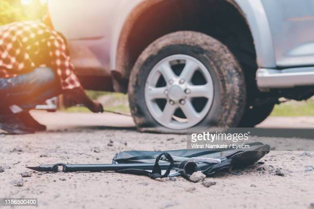 mechanic repairing car puncture on road - puncturing stock pictures, royalty-free photos & images