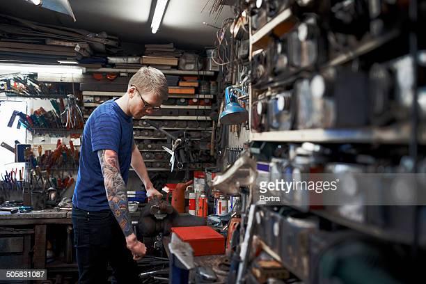 Mechanic repairing machine part in garage