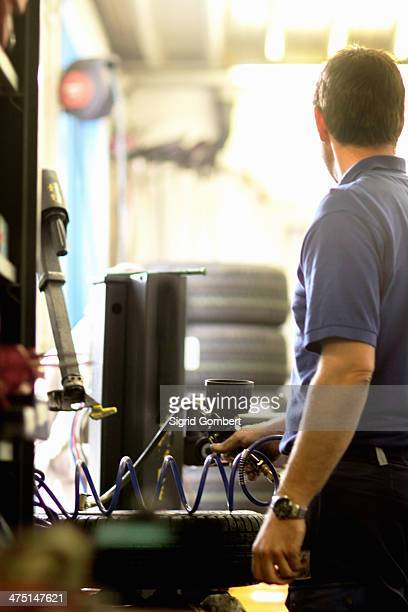 mechanic repairing wheel in workshop - sigrid gombert stock pictures, royalty-free photos & images