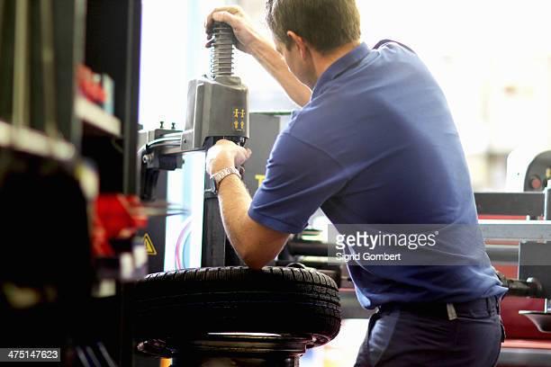 mechanic repairing wheel in workshop - sigrid gombert stock-fotos und bilder