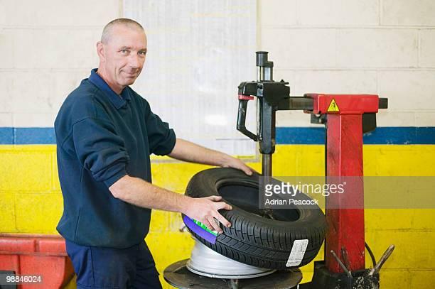 Mechanic replacing tire on car rim