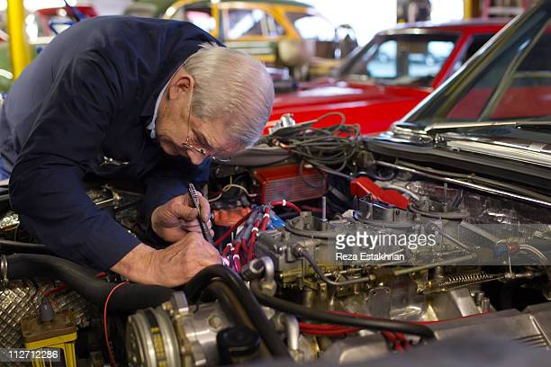 Mechanic searches with flashlight in auto engine