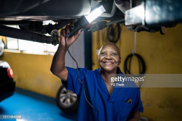 mechanic senior woman checking car in car repair shop - one senior woman only stock pictures, royalty-free photos & images