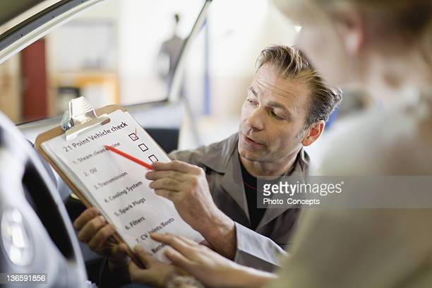 Mechanic showing checklist to customer