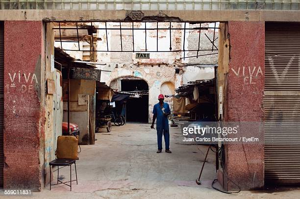 mechanic standing in front of repair shop - auto repair shop exterior stock pictures, royalty-free photos & images