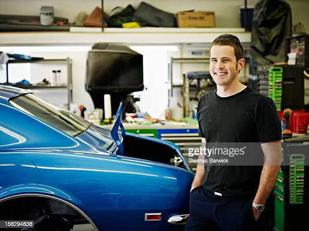 Mechanic standing in garage next to classic car