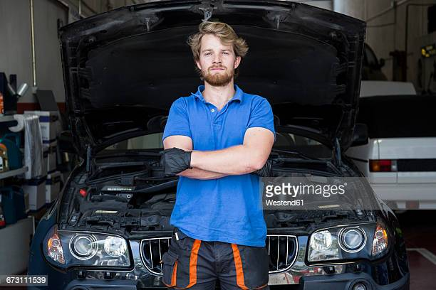 Mechanic standing in his car workshop with arms crossed