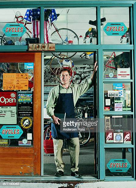 mechanic stands leaning on the entrance to his bicycle shop - bicycle shop stock pictures, royalty-free photos & images