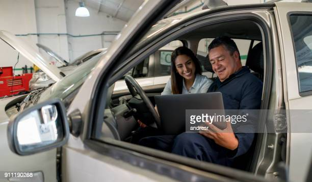 Mechanic talking to a female customer in a car at a garage