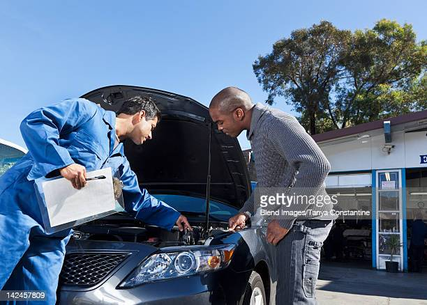 Mechanic talking to customer about car engine