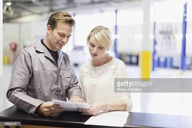 mechanic talking to customer in garage - auto repair shop stock pictures, royalty-free photos & images