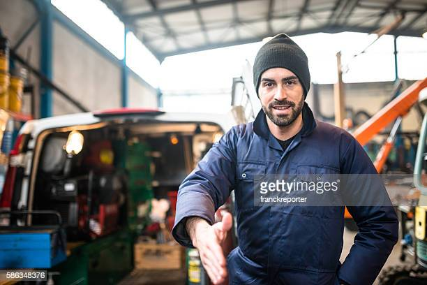 mechanic technician on a garage give the handshake