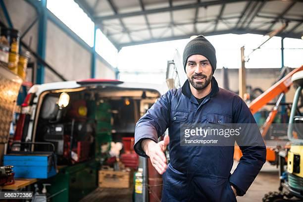 mechanic technician on a garage give the handshake