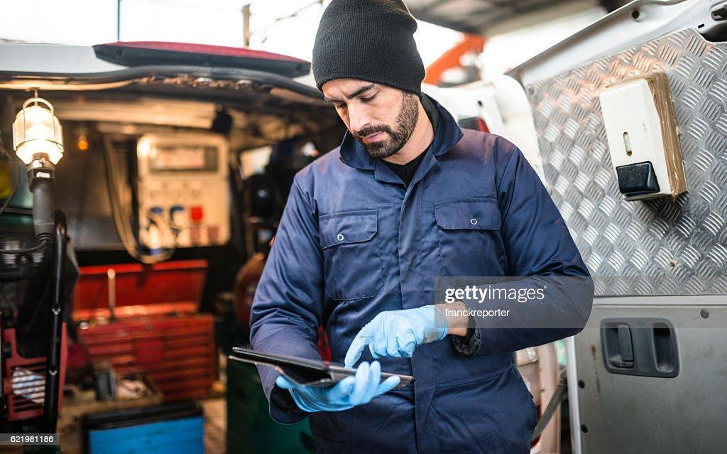 mechanic technician on a garage : Stock Photo